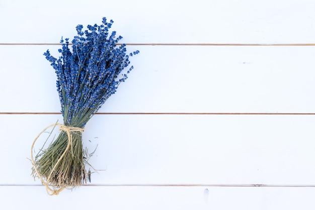 Bouquet et fleurs de lavande sur planche de bois blanc