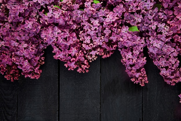 Bouquet de fleurs lilas sur fond en bois noir.