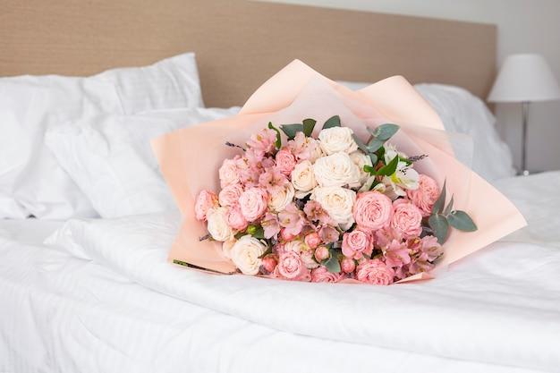 Bouquet de fleurs sur le lit de l'hôtel, cadeau
