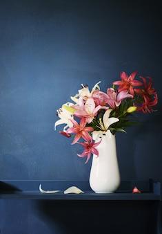 Bouquet de fleurs de lys dans un vase sur fond sombre
