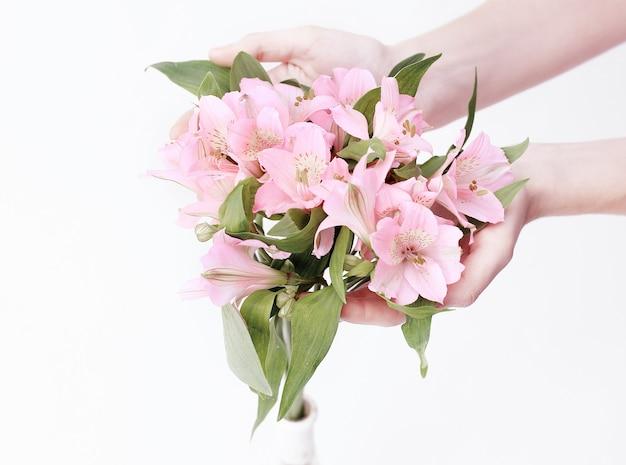 Bouquet de fleurs en mains féminines isolé sur fond clair