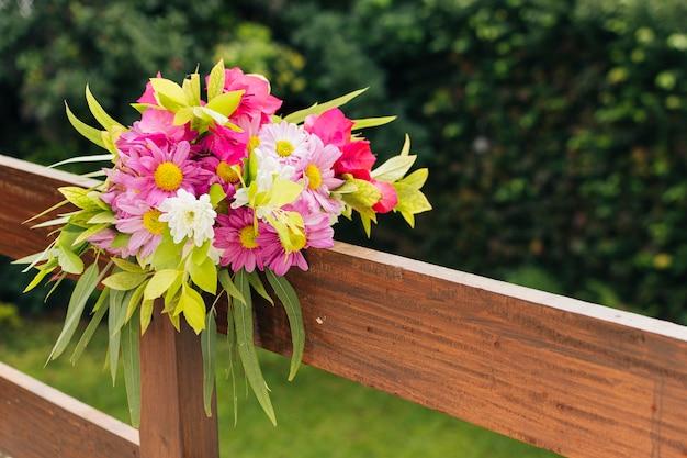 Bouquet de fleurs de mariage coloré noué sur une balustrade en bois