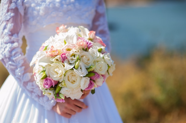 Bouquet de fleurs de mariage dans les mains de la mariée avec une robe blanche