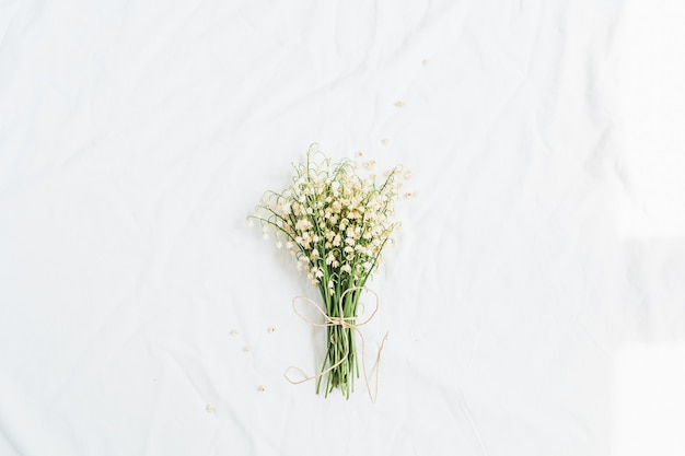 Bouquet de fleurs de muguet sur une surface blanche