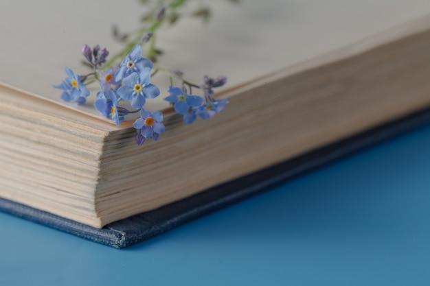Bouquet de fleurs de myosotis et très vieux livre