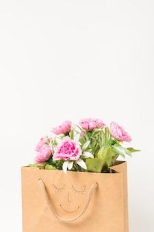 Bouquet de fleurs d'oeillets roses à l'intérieur d'un sac en papier brun