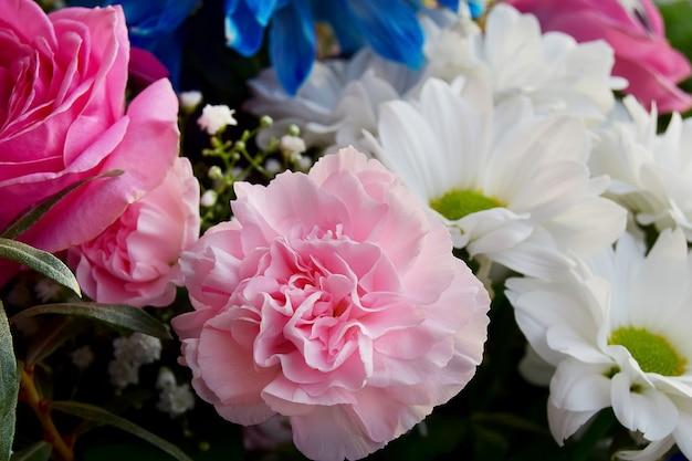 Bouquet de fleurs d'oeillets roses et de roses, chrysanthèmes blancs et bleus, gros plan. filtre doux.