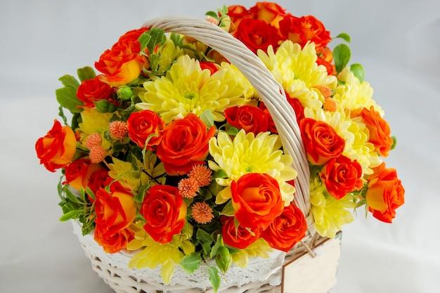 Bouquet de fleurs panier en osier avec roses rouges et chrysanthèmes jaunes dans une boîte cadeau