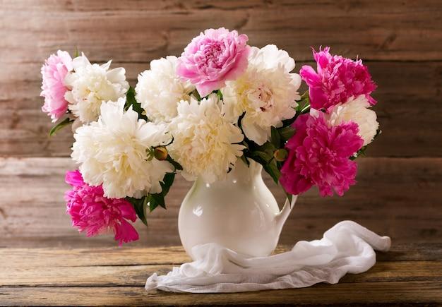 Bouquet de fleurs de pivoines colorées dans un pot blanc sur table en bois