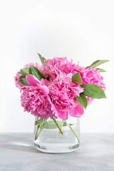 Bouquet de fleurs de pivoines roses dans un cadre rose pastel. copier l'espace pour le texte. vue de dessus. lay plat.