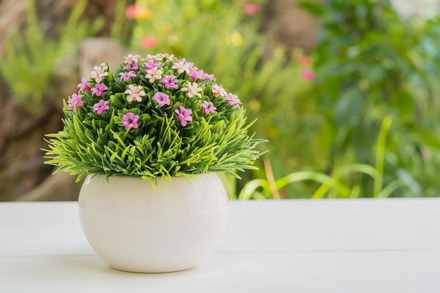 Bouquet de fleurs en plastique dans un pot placé sur une bûche de bois blanche dans le jardin.