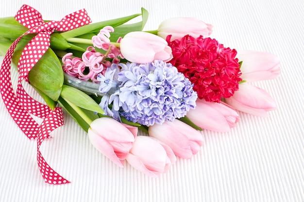 Bouquet de fleurs printanières orné de ruban sur nappe blanche soft focus