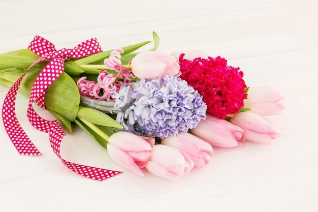 Bouquet de fleurs printanières orné de ruban sur une table en bois blanc. vue de dessus, flou