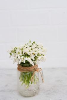 Bouquet de fleurs printanières de perce-neige dans un vase en verre sur un mur de briques claires.