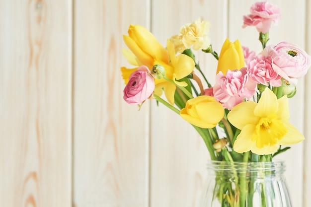 Bouquet de fleurs printanières: tulipes, oeillets, renoncules et jonquilles en vase sur table. salutation de la fête des mères