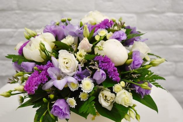 Bouquet de fleurs de printemps dans une élégante boîte à chapeau sur tableau blanc.