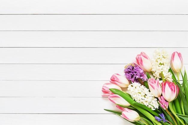 Bouquet de fleurs de printemps sur fond en bois blanc. vue de dessus, copiez l'espace.