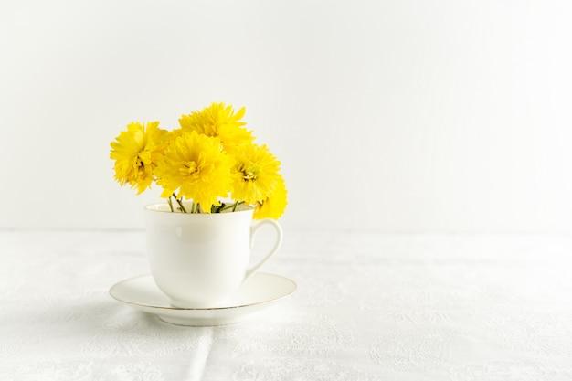 Bouquet de fleurs de printemps jaune dans une tasse de thé blanc