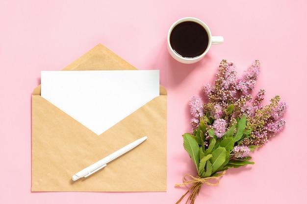 Bouquet de fleurs roses, enveloppe avec carte vierge blanche