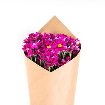 Bouquet de fleurs roses enveloppé de papier brun sur fond blanc
