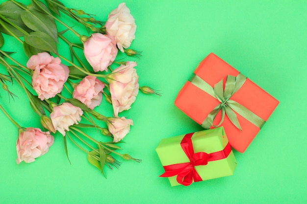 Bouquet de fleurs roses avec feuilles et coffrets cadeaux avec ruban sur fond vert. vue de dessus. concept de jour de célébration.