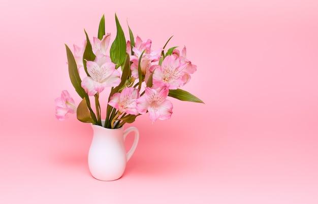 Bouquet de fleurs roses sur fond rose. fleurs de printemps dans un vase blanc. minimalisme.