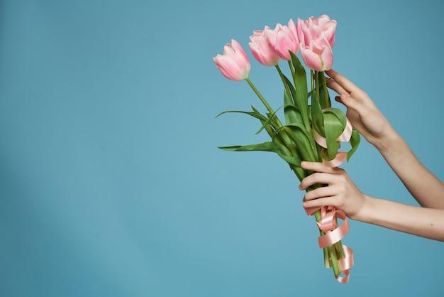 Bouquet de fleurs roses à la main cadeau romance fond bleu
