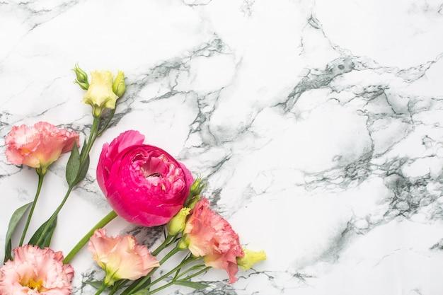 Bouquet de fleurs roses renoncules sur fond de marbre avec copyspace
