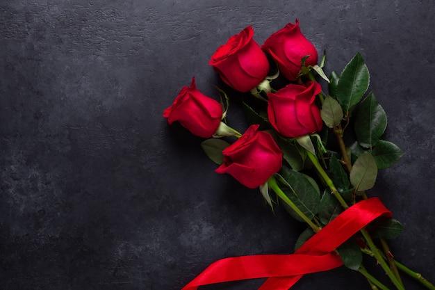 Bouquet de fleurs roses rouges sur pierre noire.