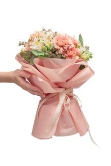 Bouquet de fleurs roses tendres dans du papier d'emballage rose dans les mains de la femme isolées sur une surface blanche