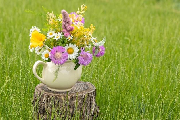 Un bouquet de fleurs sauvages dans une ancienne petite théière de village sur fond d'herbe verte. copiez l'espace.
