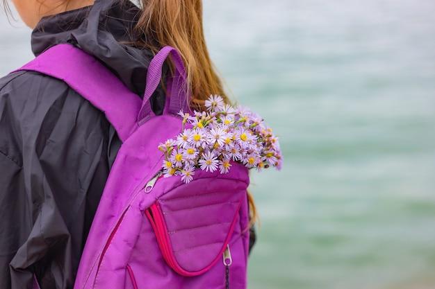 Un bouquet de fleurs sauvages dans un sac à dos de sport d'une fille