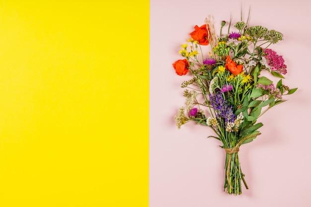 Bouquet de fleurs sauvages sur fond de fond rose et jaune