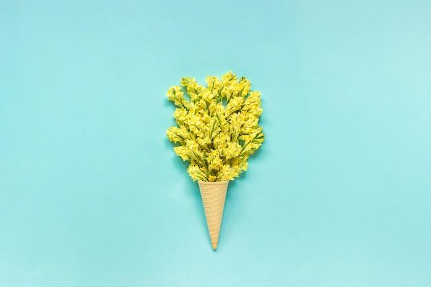 Bouquet de fleurs sauvages jaunes dans le cornet de crème glacée à la gaufre sur fond bleu concept bonjour l'été