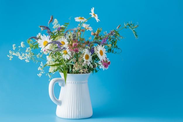 Bouquet de fleurs sauvages en pot sur fond bleu uni