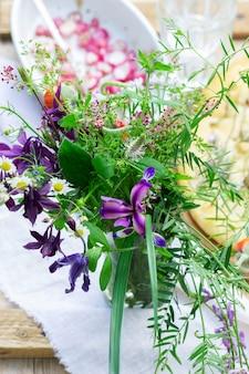 Un bouquet de fleurs sauvages, de radis au four et de focaccia sur une table en bois. style rustique, mise au point sélective.