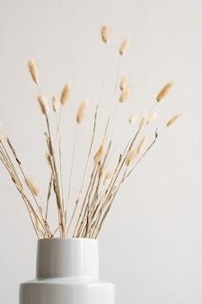 Bouquet de fleurs sauvages séchées ou de pointes à l'intérieur d'un vase en céramique blanche sur le mur ou avec copyspace pour votre message ou annonce