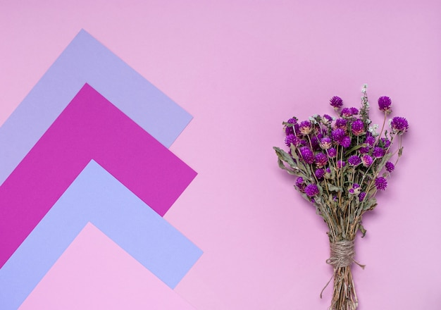 Bouquet de fleurs sauvages sèches sur une surface rose, violette et lilas