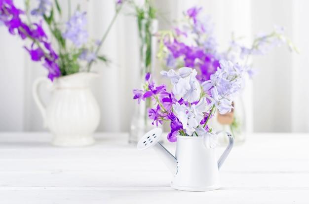 Bouquet de fleurs sauvages violettes dans un vase en verre sur un tableau blanc à l'intérieur