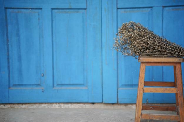 Bouquet de fleurs séchées sur une chaise en bois près de la porte bleue