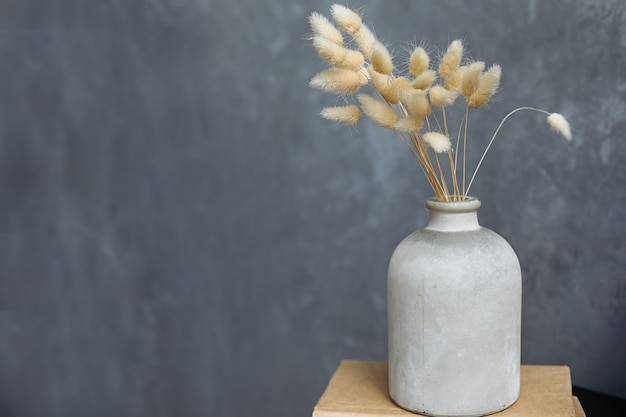 Un bouquet de fleurs séchées dans une céramique blanche sur fond gris