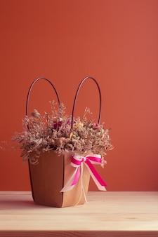 Bouquet de fleurs séchées dans une corbeille en papier rose avec espace copie