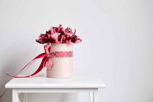 Bouquet de fleurs séchées avec des herbes dans une boîte à chapeau ronde rose dans une chambre avec un mur blanc