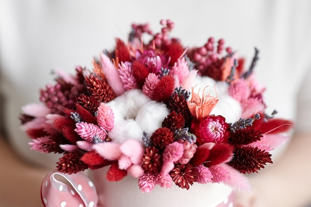 Bouquet de fleurs séchées avec des herbes dans une boîte à chapeau ronde rose dans les mains