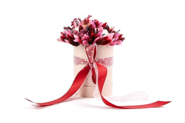 Bouquet de fleurs séchées avec des herbes dans une boîte à chapeau ronde rose isolé sur fond blanc