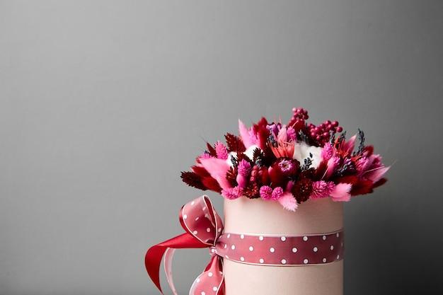 Bouquet de fleurs séchées avec des herbes dans une boîte à chapeau ronde rose