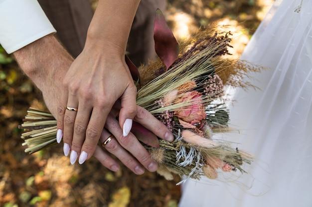 Le bouquet de fleurs séchées de la mariée entre les mains des mariés.