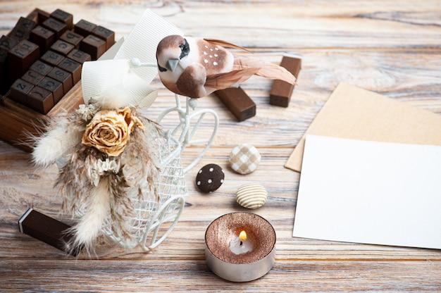 Bouquet de fleurs séchées sur vélo décoratif avec petit oiseau brun et bougie allumée sur la table. carte de voeux pour mariage ou vacances dans des tons naturels