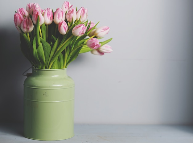 Bouquet de fleurs de tulipe rose fraîche sur une étagère en face du mur de pierre. afficher avec copie espace
