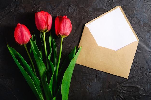 Bouquet de fleurs de tulipe rouge avec carte enveloppe sur fond noir texturé, vue de dessus copie espace